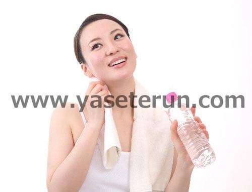 軽い運動をした後に水分補給をする女性