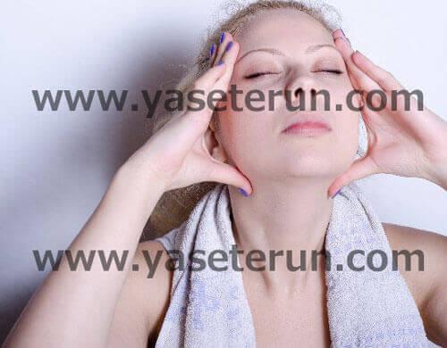 首にタオルをまき両手を顔に上に持ち上げながら瞑想する女性