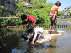 川にある大きな石にのり川遊びする子供たち