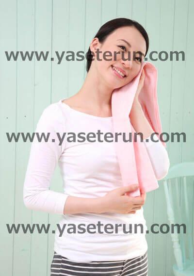 左手にピンク色のタオルで運動後汗を拭きとる女性