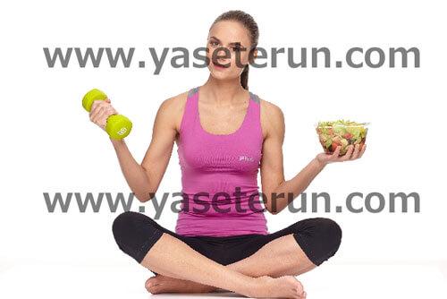 左手にサラダ右手にダンベルを持ち男座りをする女性