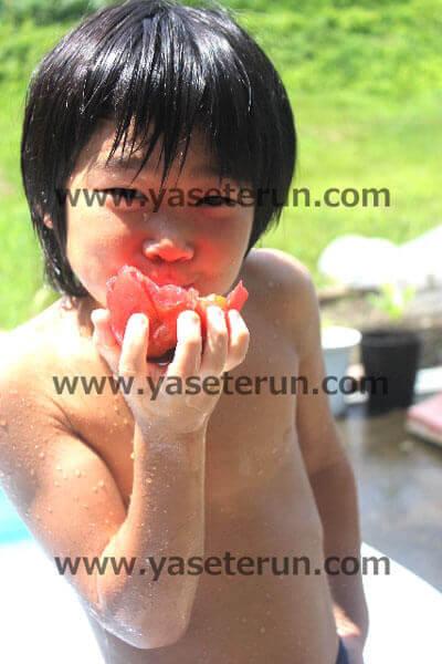 海遊びでグアバを丸かじりする少年