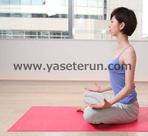 室内で座禅を組み瞑想する女性