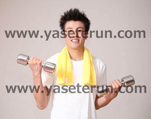 両腕に軽量ダンベルを持ちながら筋力トレーニングする男性