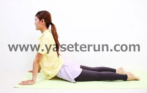 背中の筋肉を伸ばそうと背筋ストレッチをする学生